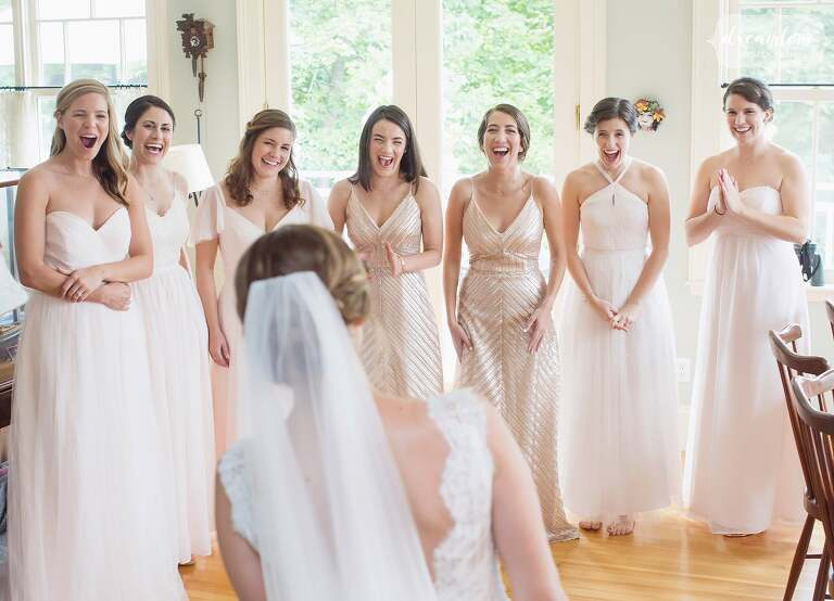 Bridesmaids see the bride in her dress for the first time at this North Shore wedding in MA.