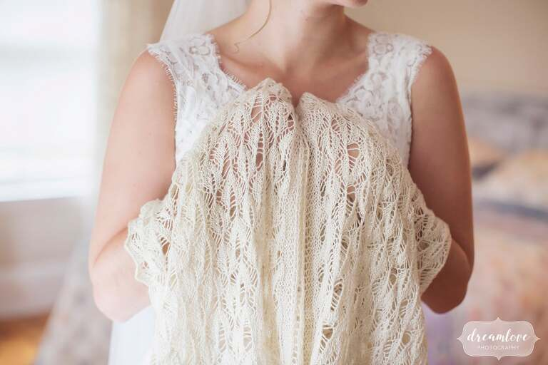 The bride holds a handmade wedding crochet wrap her mom made in Manchester, MA.