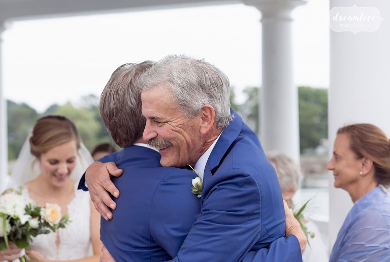 Father of the groom hugs the father of the bride in Manchester, MA.