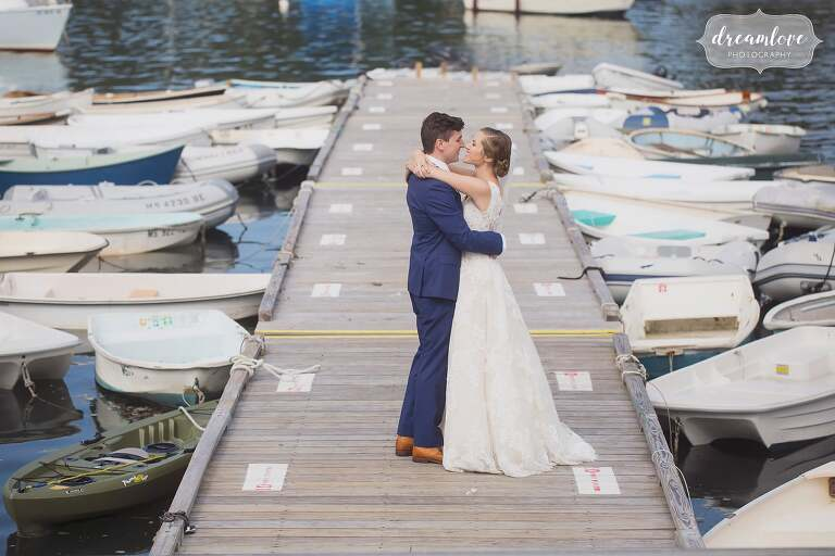 The bride and groom pose on the dock surrounded by boats in Tuck's Point, MA.