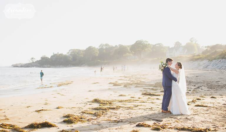The bride and groom wrap their arms around each other on Singing Beach by the ocean near Boston.