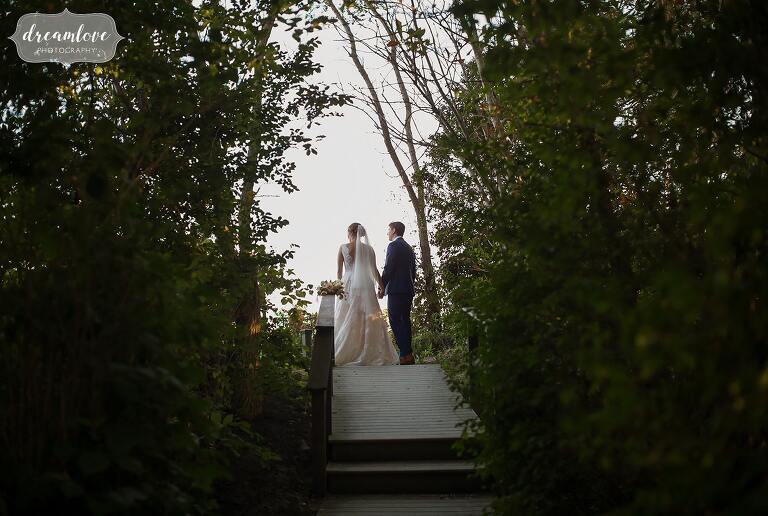 The bride and groom stand at the end of a boardwalk above the Singing Beach.