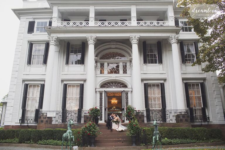 Bride and groom sit on the steps of their Linden Place wedding venue in RI.