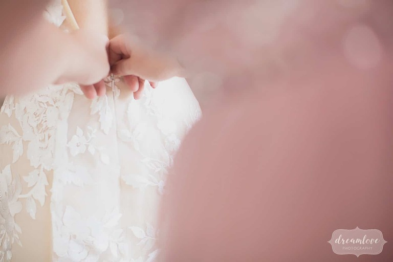 The bride's sister helps her zip up the dress in this candid wedding photo at the Linden Place.