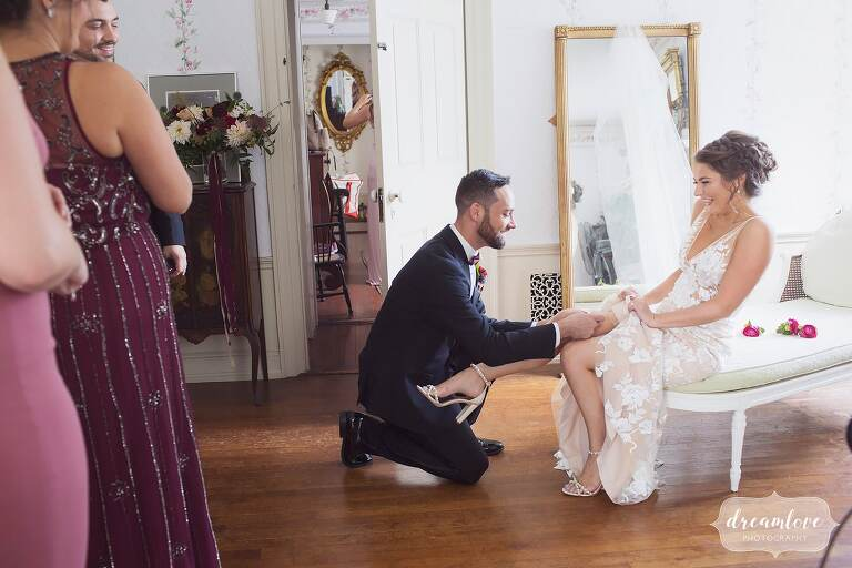 The bride's best friend in this mixed gender wedding party helps her put the garter belt on.