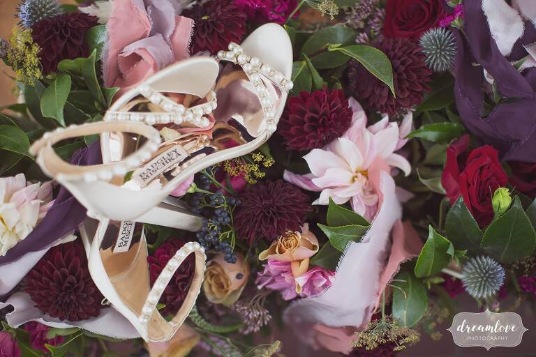 Artistic wedding photography of the bride's shoes on the wedding flowers for this Bristol, RI wedding.