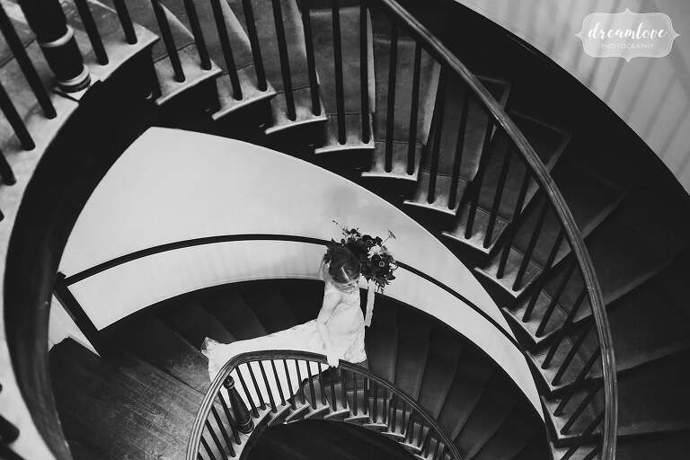 Artsy wedding photo of bride walking down spiral staircase at the Linden Place.