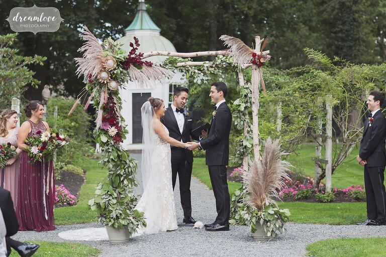 The chuppah is decorated with floral garlands for September RI wedding.