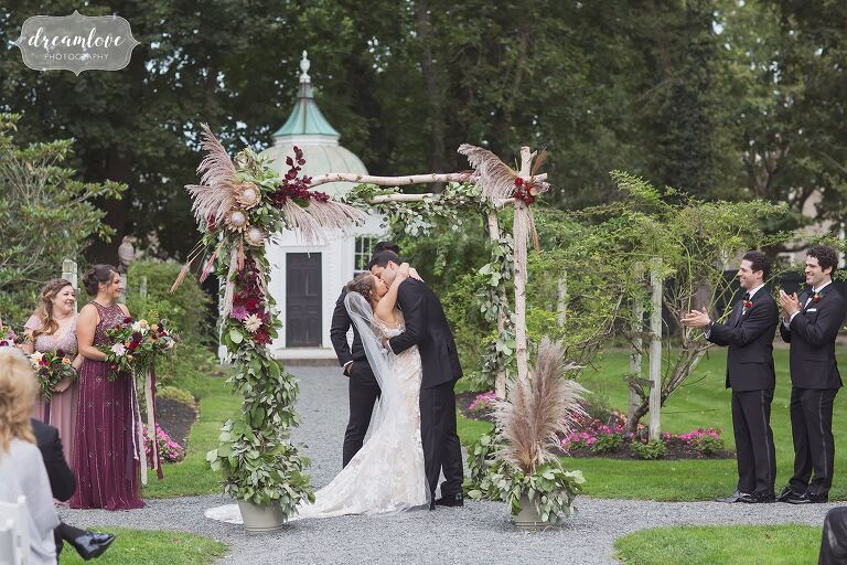The bride and groom kiss at end of their ceremony at Linden Place.