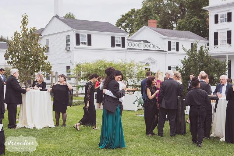 Guests enjoy cocktails on the lawn at this outdoor estate wedding venue in RI.