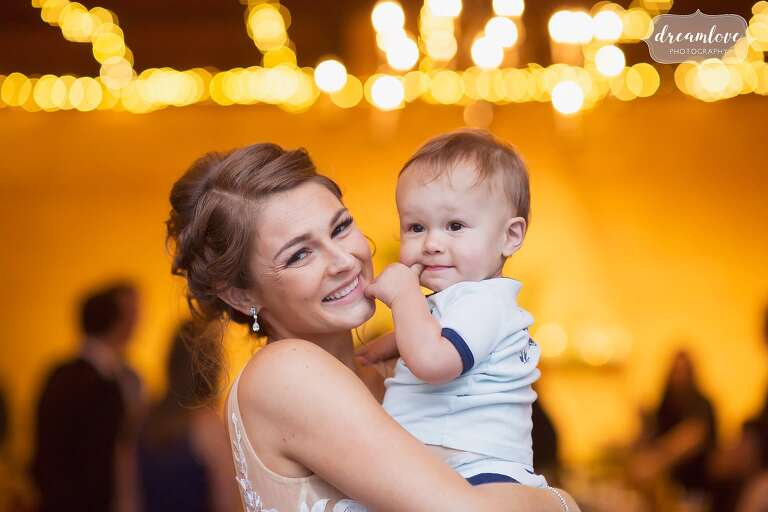 Amazing wedding photo of the bride with her nephew and blurry string lights at RI wedding.