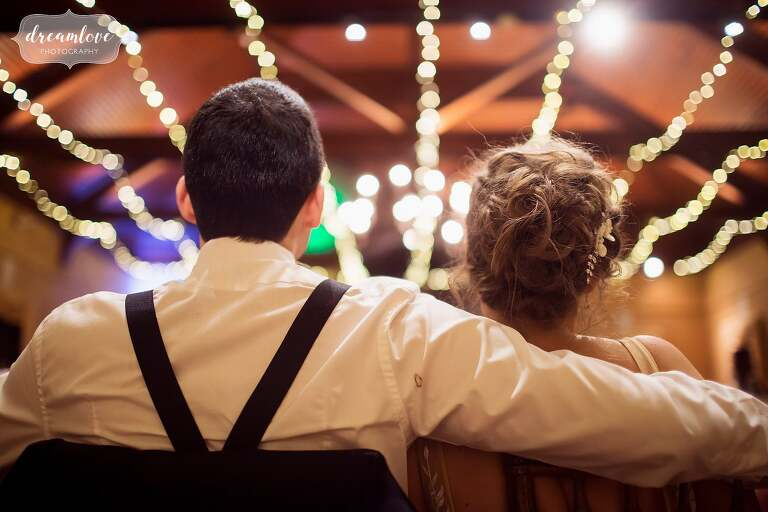 Bride and groom sit in chairs listening to speeches with blurry lights.
