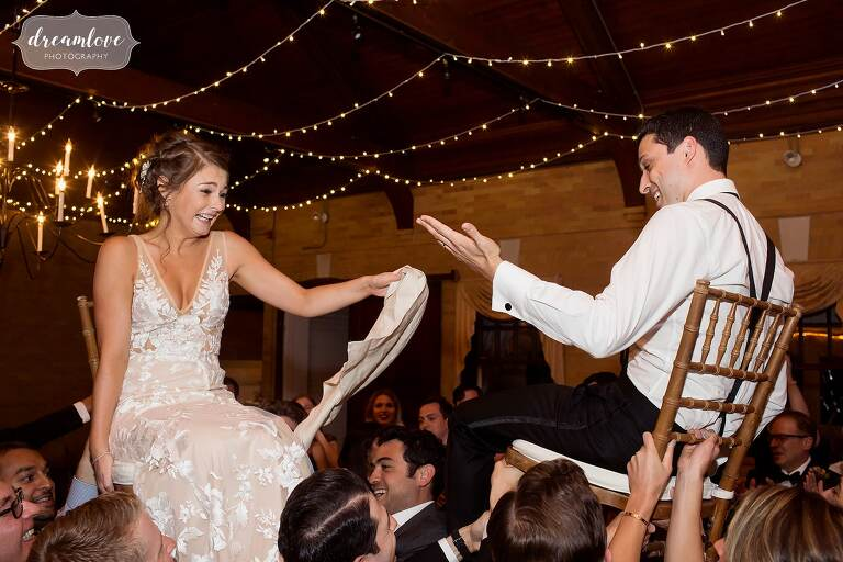 The bride and groom lifted up on chairs during the hora jewish dance at Linden Place.