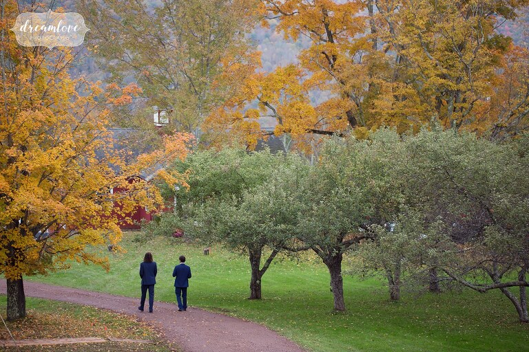Two groomsmen walk through fall color trees for this Catskills wedding in Roxbury, NY.