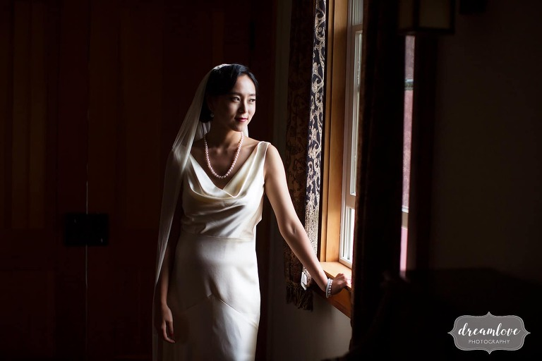 The bride looks out of the window in this fashion style wedding photo in Roxbury.