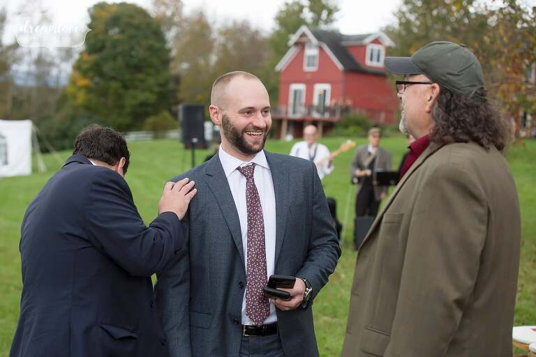 The groom laughs with friends before his October wedding in the Catskills.