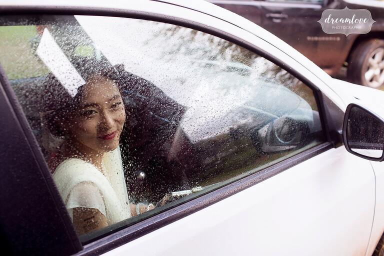 Fine art portrait of the bride looking out of a rainy window with raindrops in the Catskills.
