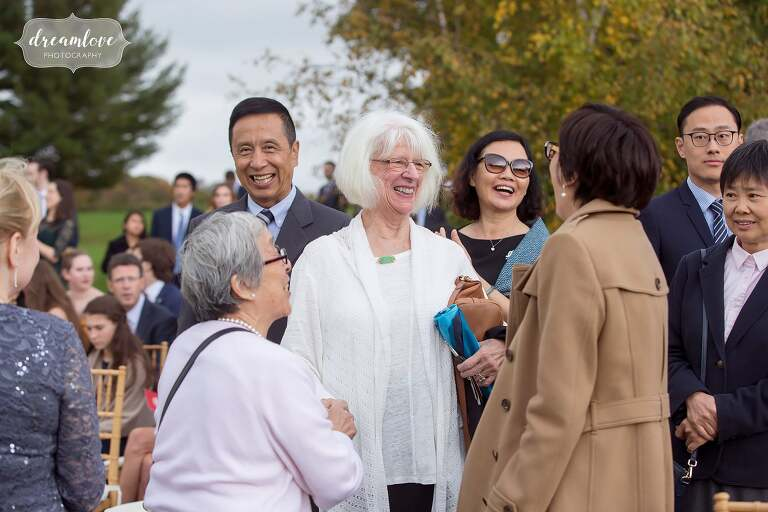 Candid wedding photos of guests talking before this outdoor ceremony in upstate NY.
