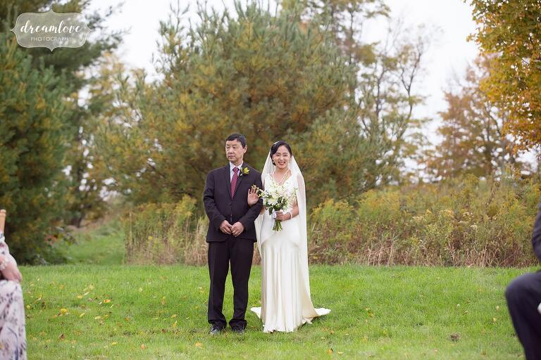 The bride and her father walk down the aisle for this Catskills backyard wedding in NY.