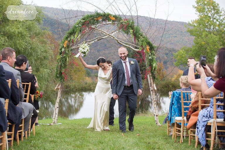 The bride and groom exit their outdoor ceremony in October in the Catskills.