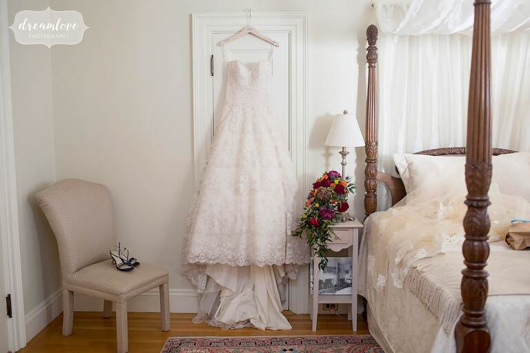 The bride's dress hangs in one of the rooms at this Glen Magna Farms October wedding.
