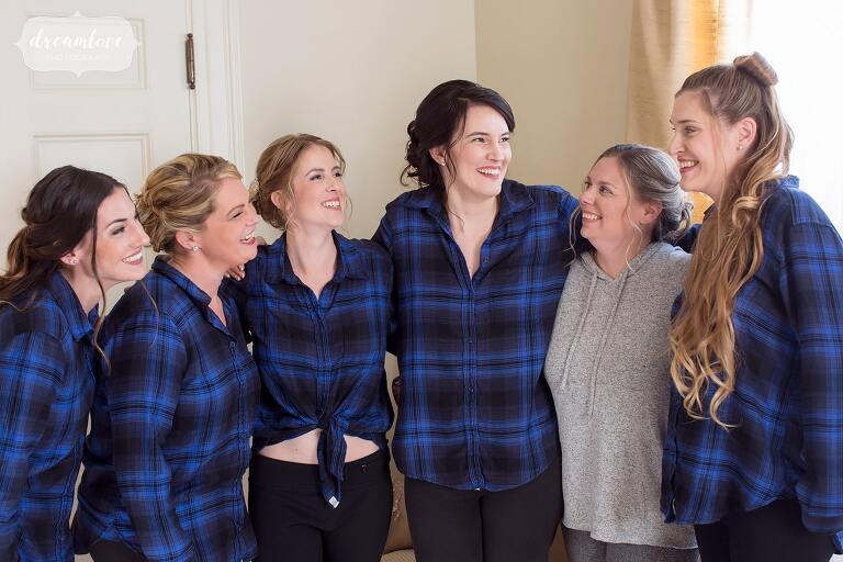 The bride and bridesmaids wear blue plaid shirts before this Glen Magna Farms October wedding.