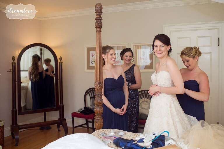 The bride puts her dress on at this Glen Magna Farms wedding in the fall.