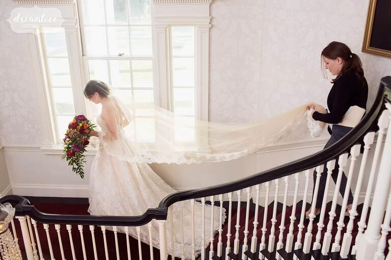 Bride walks down the staircase at the Glen Magna Farms venue.