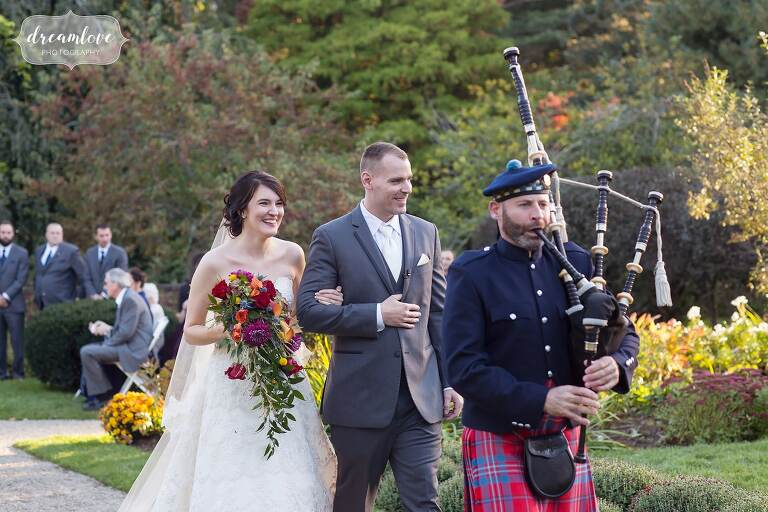 A bagpiper leads the bride and groom out of ceremony at Glen Magna.