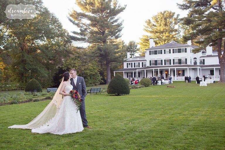Bride and groom pose in front of the mansion at the Glen Magna Farms wedding venue in Danvers, MA.