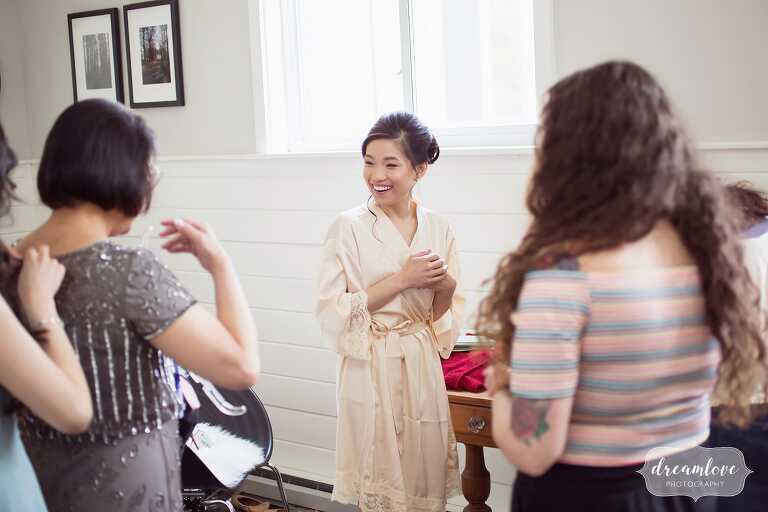 Bride getting ready for day in pink silk robe in Hudson Valley.
