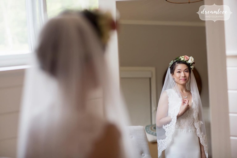 Bride looking in mirror with flower crown and veil at Hudson Valley wedding.