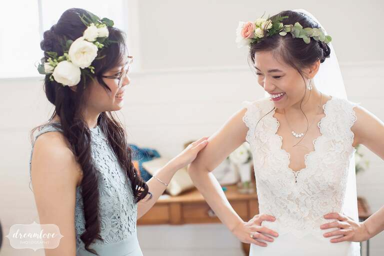 Bride laughing with sister in flower crowns at Barn at Liberty Farms.