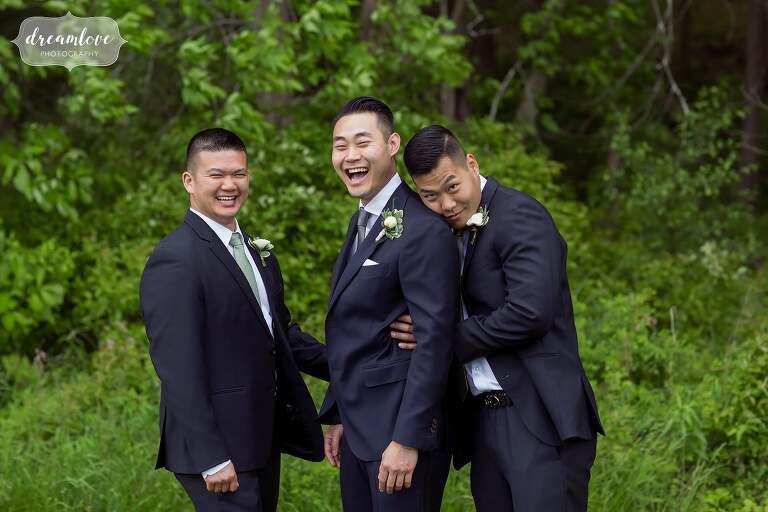 Funny groomsmen laughing at Barn at Liberty Farms.