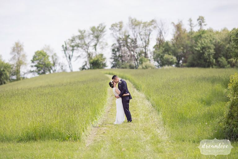 Romantic bride and groom pose in field at Barn at Liberty Farms.