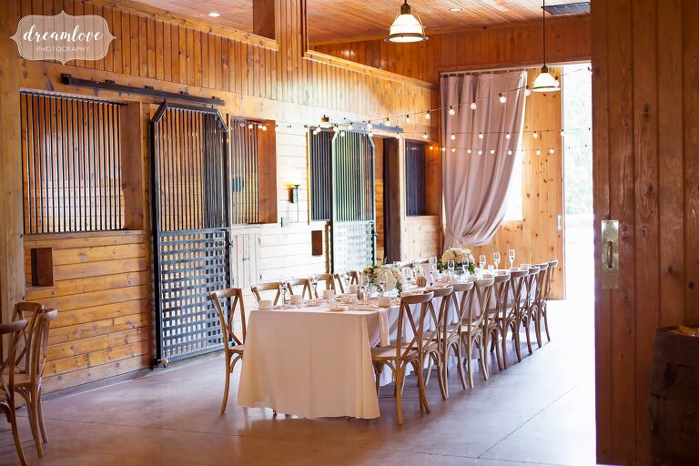 Farm tables in converted horse barn wedding venue in Hudson Valley.