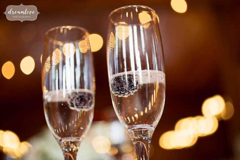 Close up photo of blackberry in champagne with bubbles at wedding.