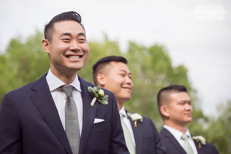 Groom smiling as bride enters outdoor ceremony in Ghent, NY.