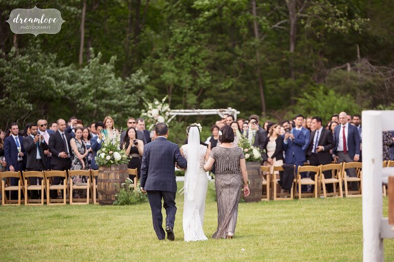 Bride walks into ceremony with parents at Barn at Liberty Farms.