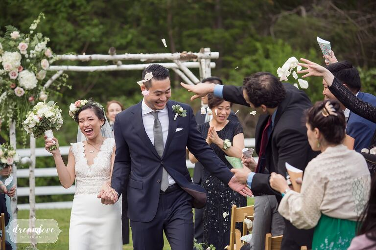 Guests throw flower petals at bride and groom as they exit ceremony at Barn at Liberty Farms.