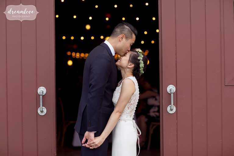 Groom kisses bride in red barn with cafe lights.