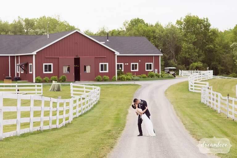 Bride and groom kiss in front of Barn at Liberty Farms venue in Hudson Valley.