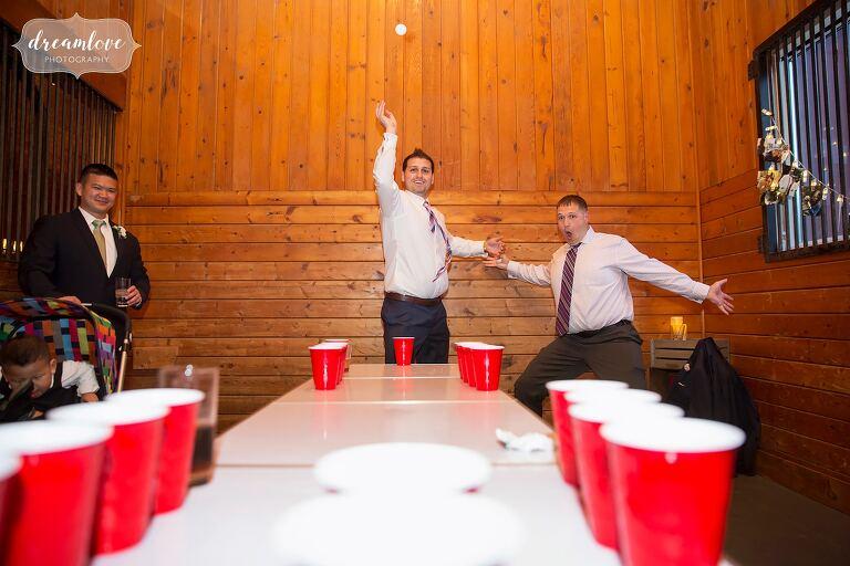 Guests play beer pong at Hudson Valley wedding.