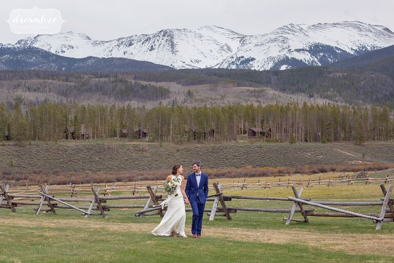 Bride and groom walk along fence at Devils Thumb Ranch near Winter Park, CO.