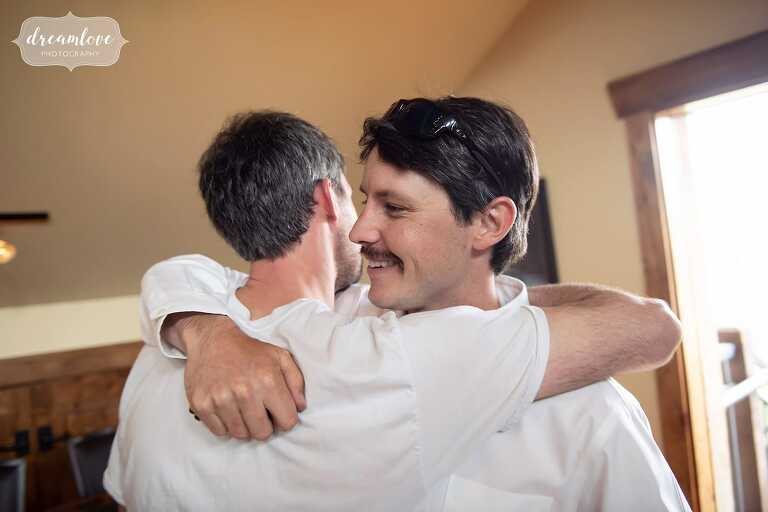 Groomsmen hugging at CO mountain ranch wedding.