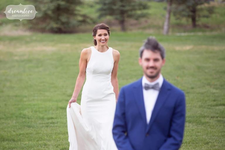 Bride walks toward groom for first look at Colorado ranch wedding.