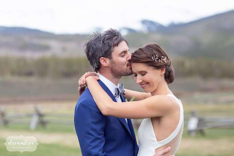 Groom kisses bride on forehead at Devil's Thumb.