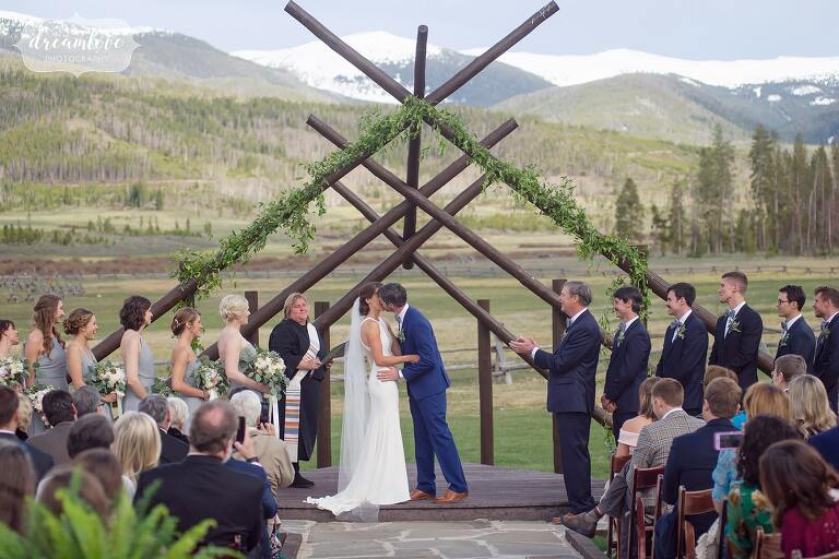 Ceremony kiss with rustic timbers and scenic rocky mountains.