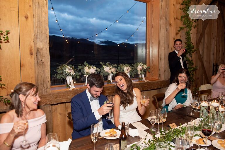 Bride and groom laugh during toasts with scenic mountain backdrop.