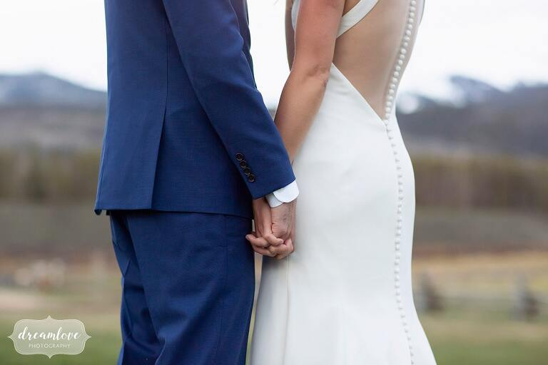 Groom in blue suit holds bride's hand.